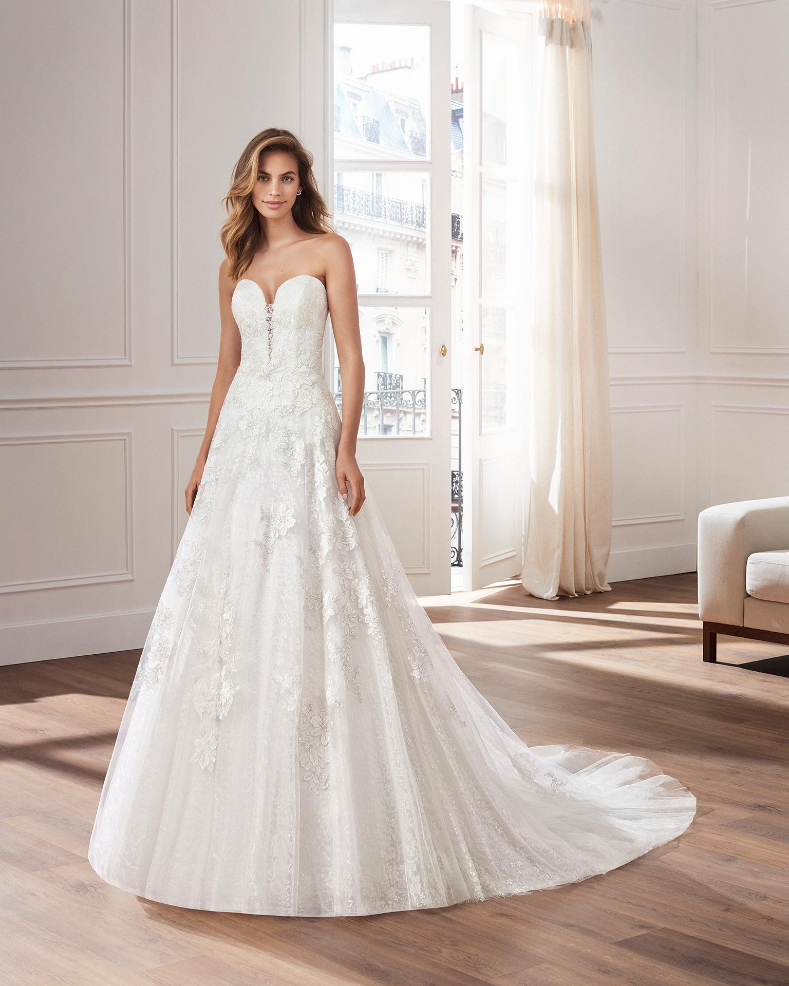 Vestido de novia corte evasé de encaje. Escote corazón, tirantes y aplicaciones en falda. Disponible en color natural. Colección  2019.