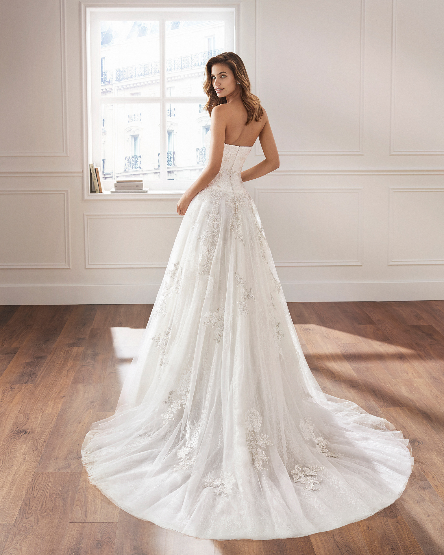 Ballgown-style wedding dress in lace. Sweetheart neckline, straps and appliquéd skirt. Available in natural. 2019  Collection.