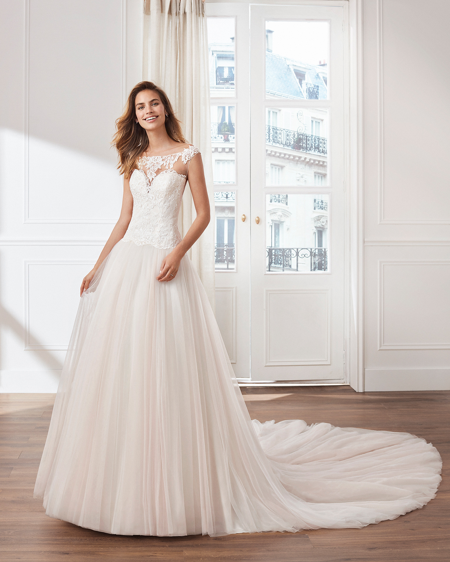 Tulle princess-style wedding dress. Illusion neckline, lace bodice and ballgown-style skirt. Available in pink and natural. 2019  Collection.