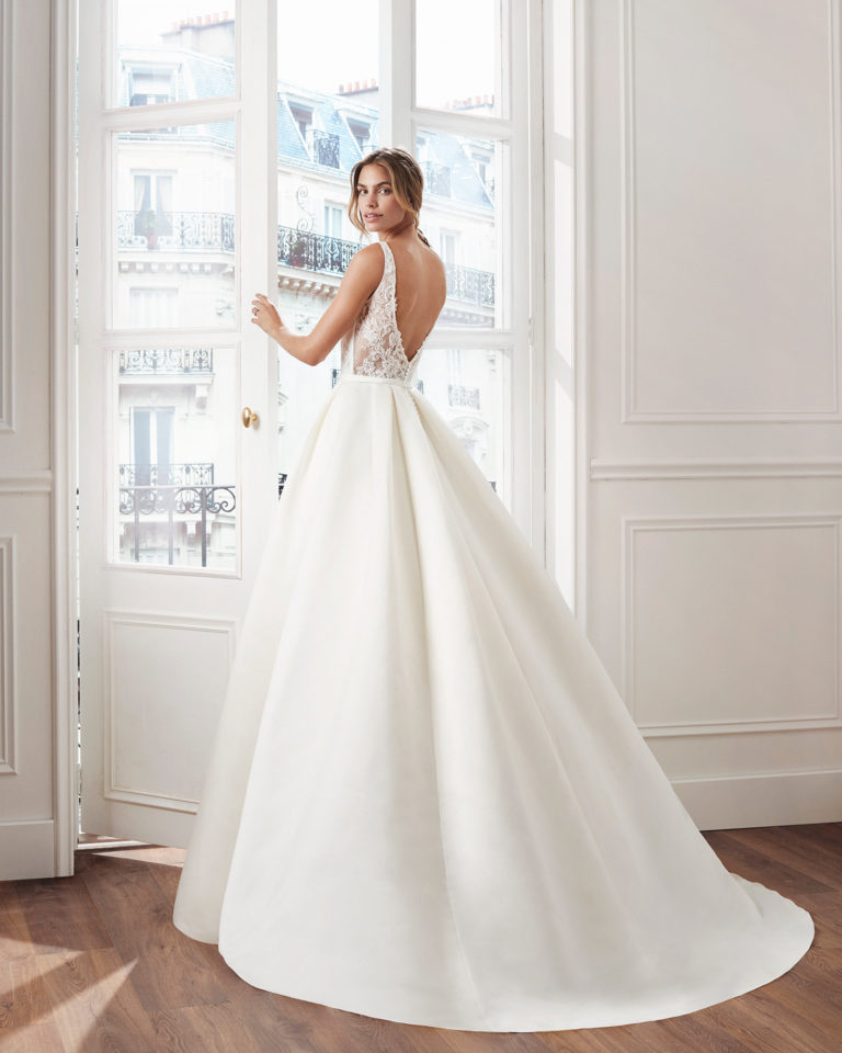 Classic A-line satin wedding dress. V-neckline, beaded lace bodice and pleats at the waist. Available in natural. 2019  Collection.