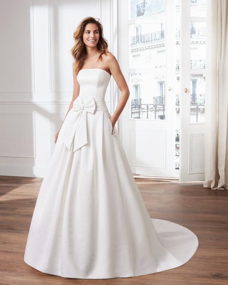 Vestido de novia estilo clásico línea A en otomán. Escote palabra de honor y lazo en cintura. Disponible en color natural. Colección  2019.
