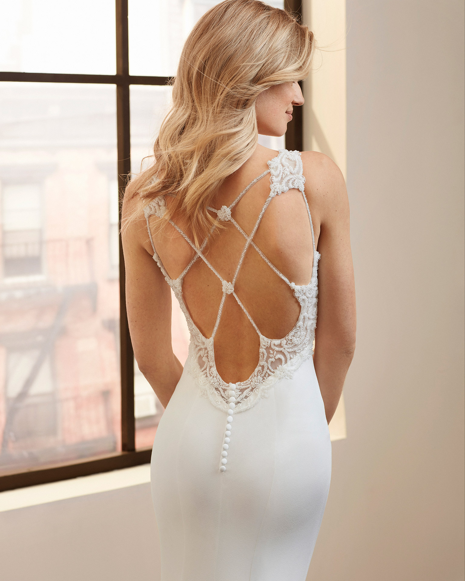 Mermaid-style wedding dress in stretch crepe with beading and back with crossover straps. 2020  Collection.