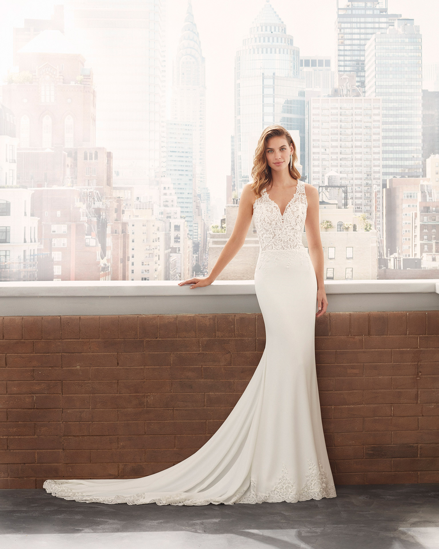 Sheath-style wedding dress in stretch crepe with lace body-shaping lining, beading at the neckline and armholes, and illusion back. 2020  Collection.