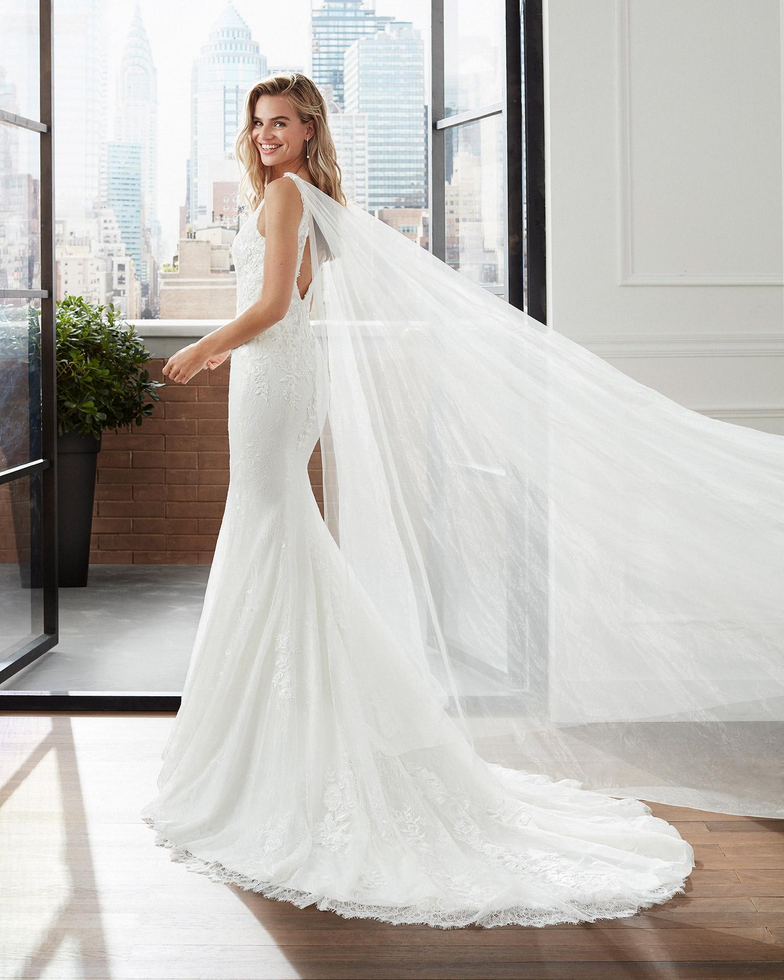 Vestido de novia corte sirena de encaje, tul y pedrería con caídas de tul y encaje con escote y espalda en V. Colección  2020.
