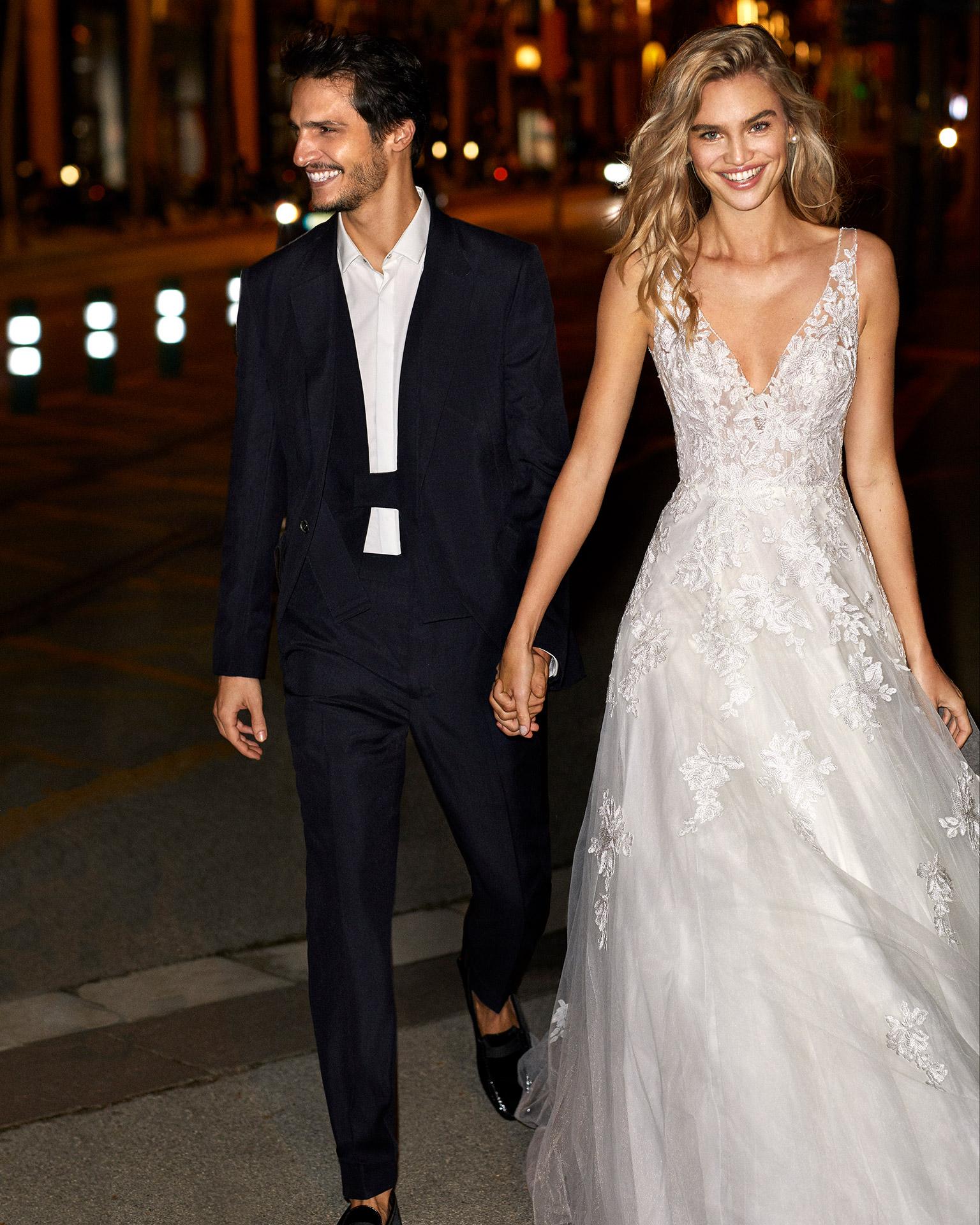 Vestido de novia de estilo romántico de encaje y tul con escote y sisa pedrería con escote y espalda en V y falda volumen. Colección  2020.