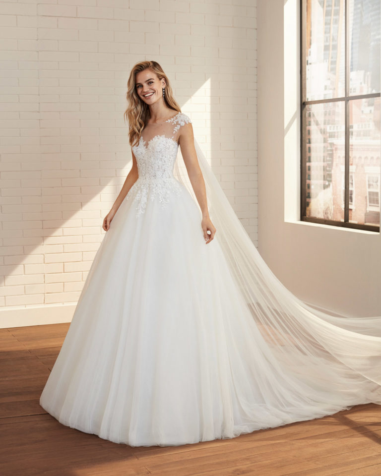 Vestido de novia de estilo romántico de tul, encaje y pedrería con escote y espalda con transparencias. Colección  2020.