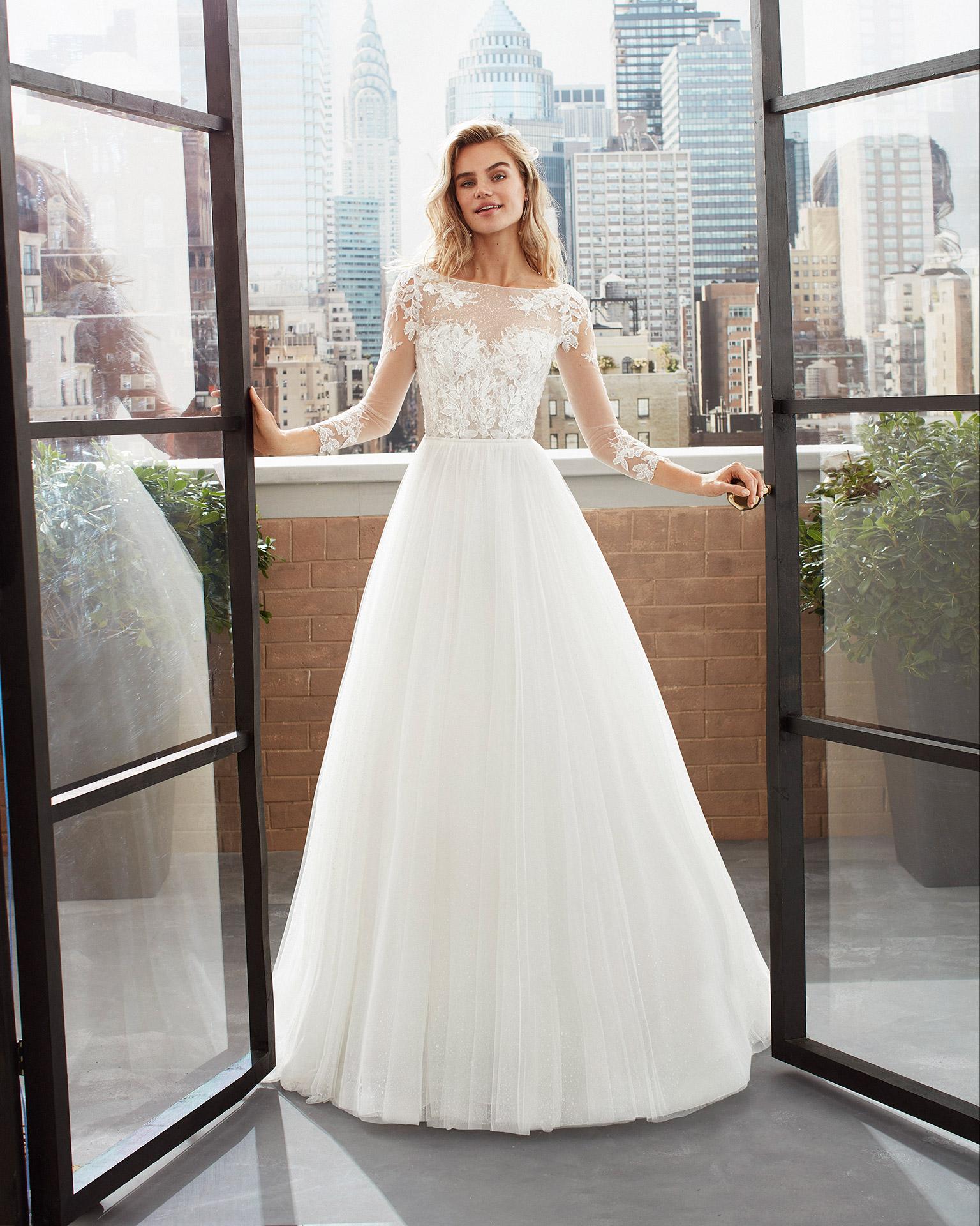 Vestido de novia de estilo romántico de tul suave, encaje y pedrería con escote corazón y manga 3/4 con espalda en V. Colección  2020.