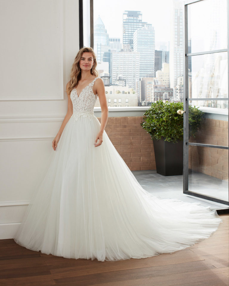 Princess-style wedding dress and overskirt in tulle, lace and crepe with V-neckline and low back. 2020  Collection.