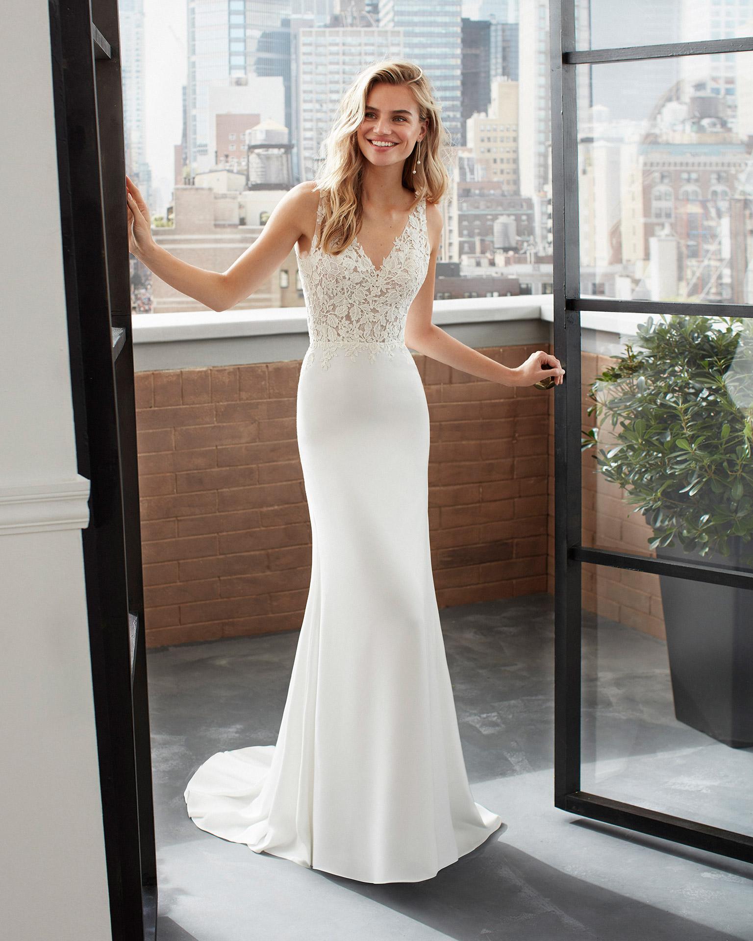 Vestido y sobrefalda de novia estilo princesa de tul, encaje y crep con escote en V y espalda escotada. Colección  2020.