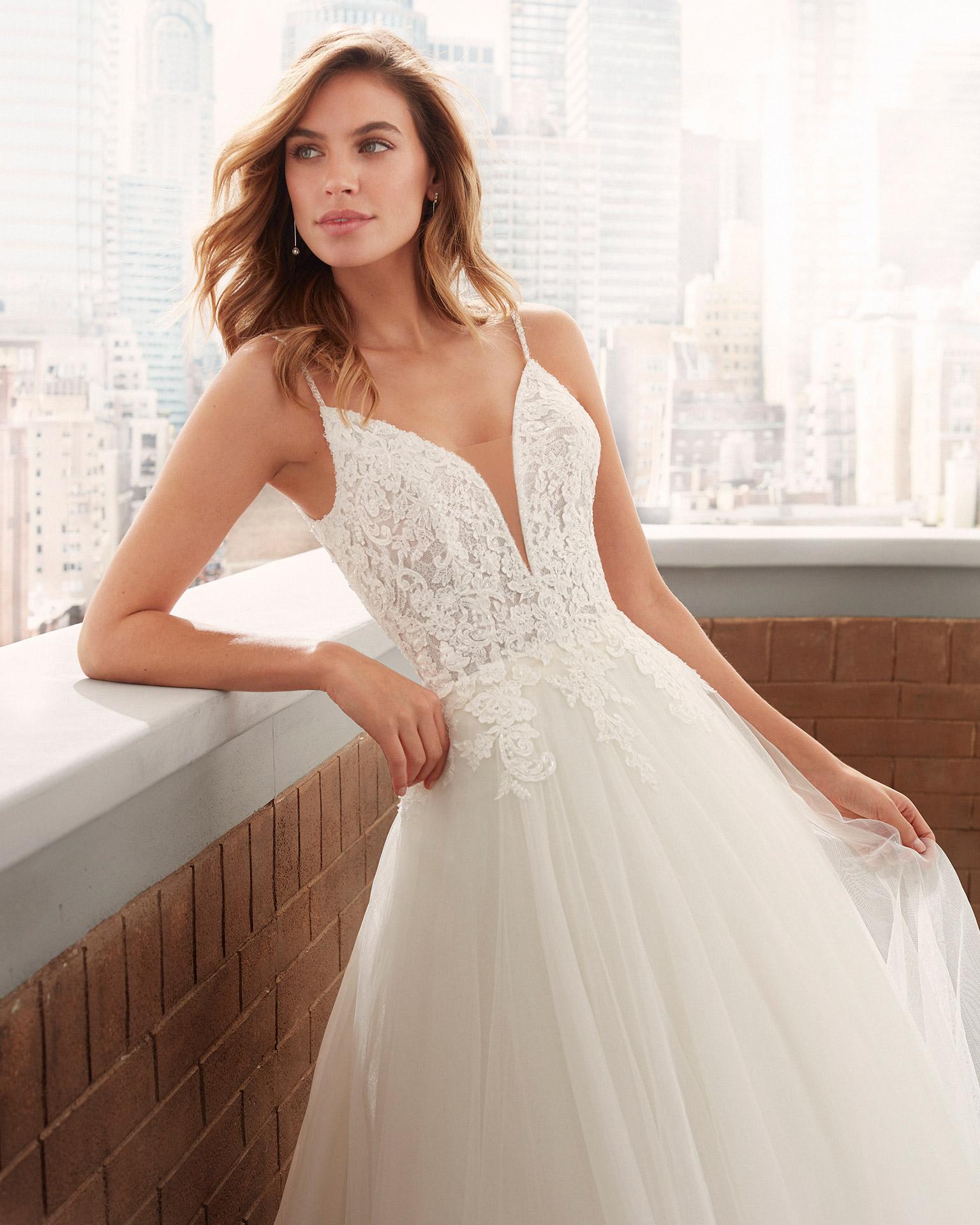 Vestido de novia estilo romántico de tul suave, encaje y pedrería con escote deep-plunge y espalda escotada. Colección  2020.