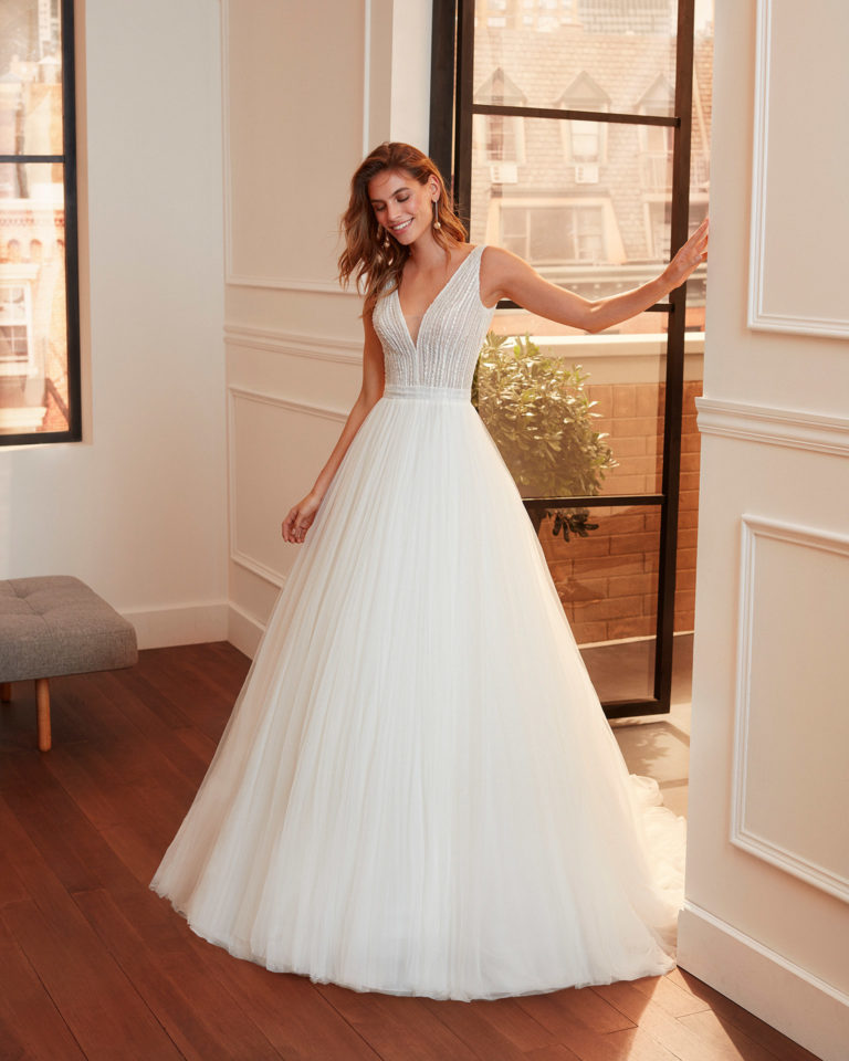 Romantic embroidered tulle wedding dress with beading, deep-plunge neckline, V-back and full skirt. 2020  Collection.