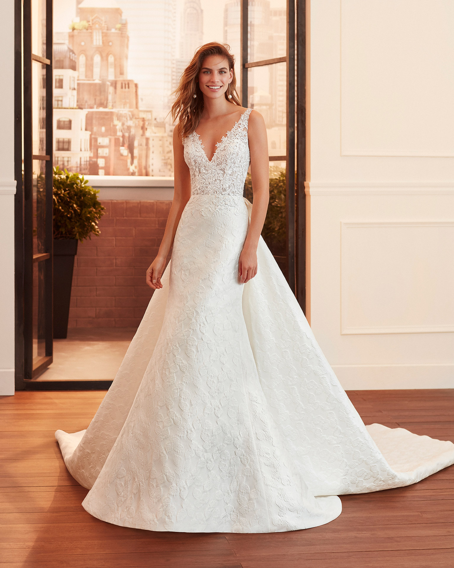 Sheath-style wedding dress and train in brocade and lace with beading, V-neckline and back with sheer inserts. 2020  Collection.