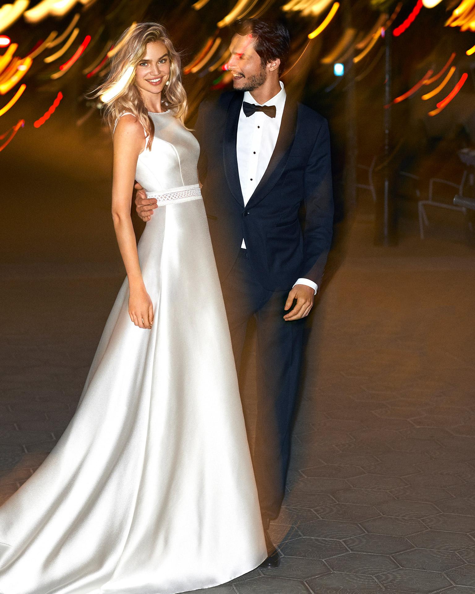 Vestido de novia estilo línea A de mikado y encaje, escote barco y espalda escotada con pasamanería. Colección  2020.