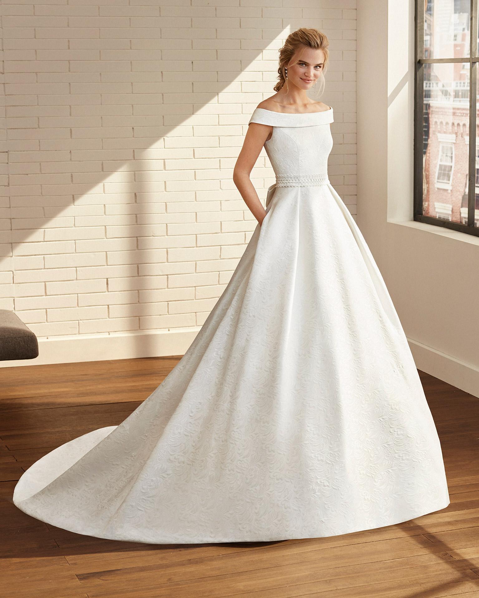 Vestido de novia estilo clásico de brocado y cinturón de encaje con escote bajo hombros. Colección  2020.