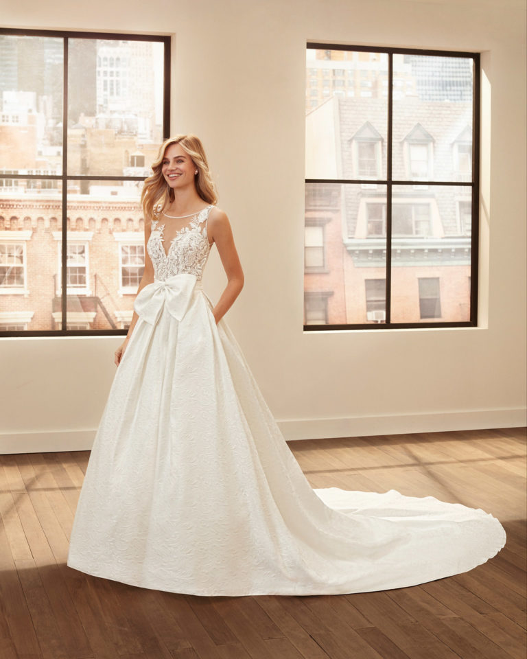 Classic brocade, crepe and lace wedding dress and overskirt with beading and neckline and back with sheer inserts. 2020  Collection.