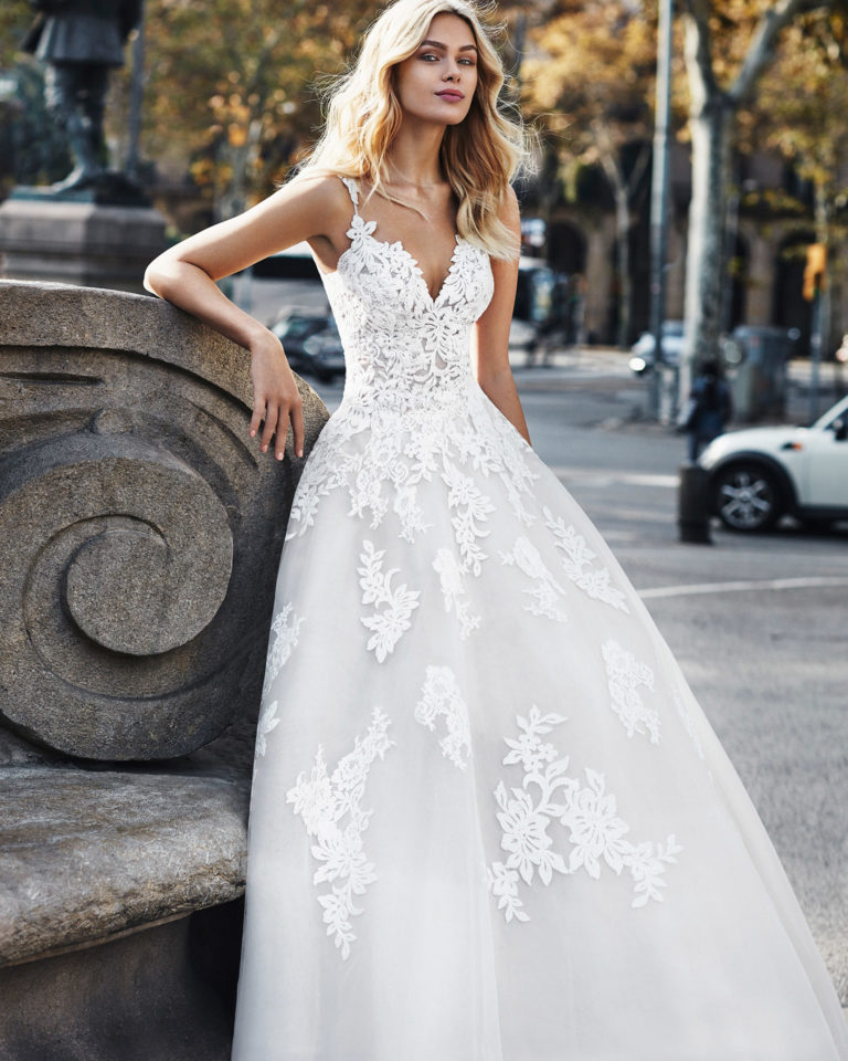 Lace princess-style wedding dress. Deep-plunge sweetheart neckline, straps, and skirt with beaded lace appliqués. Available in natural/nude and natural. 2020  Collection.