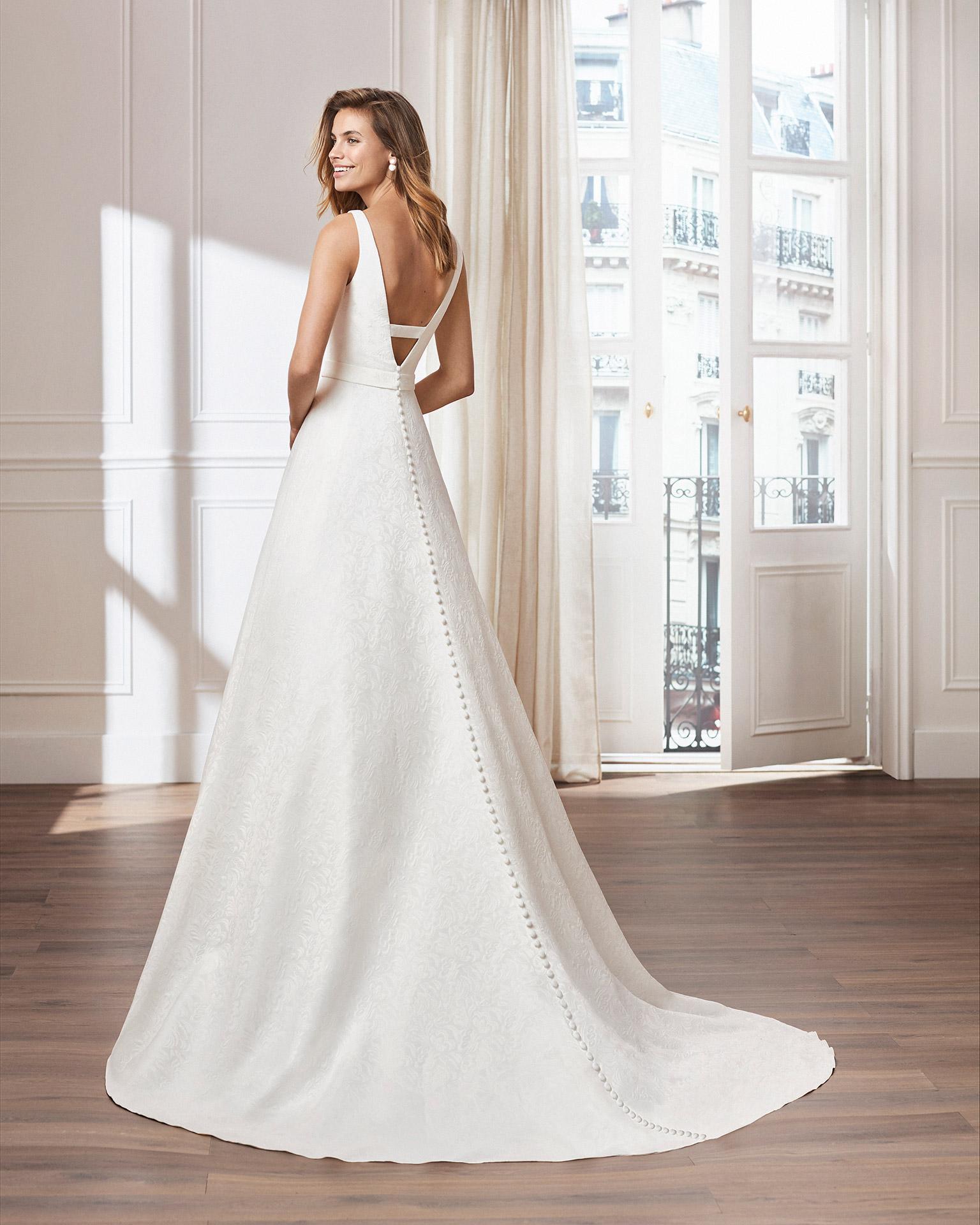 Vestido de novia estilo clásico línea A en brocado. Escote en V en cuerpo y en espalda. Disponible en color natural. Colección  2020.