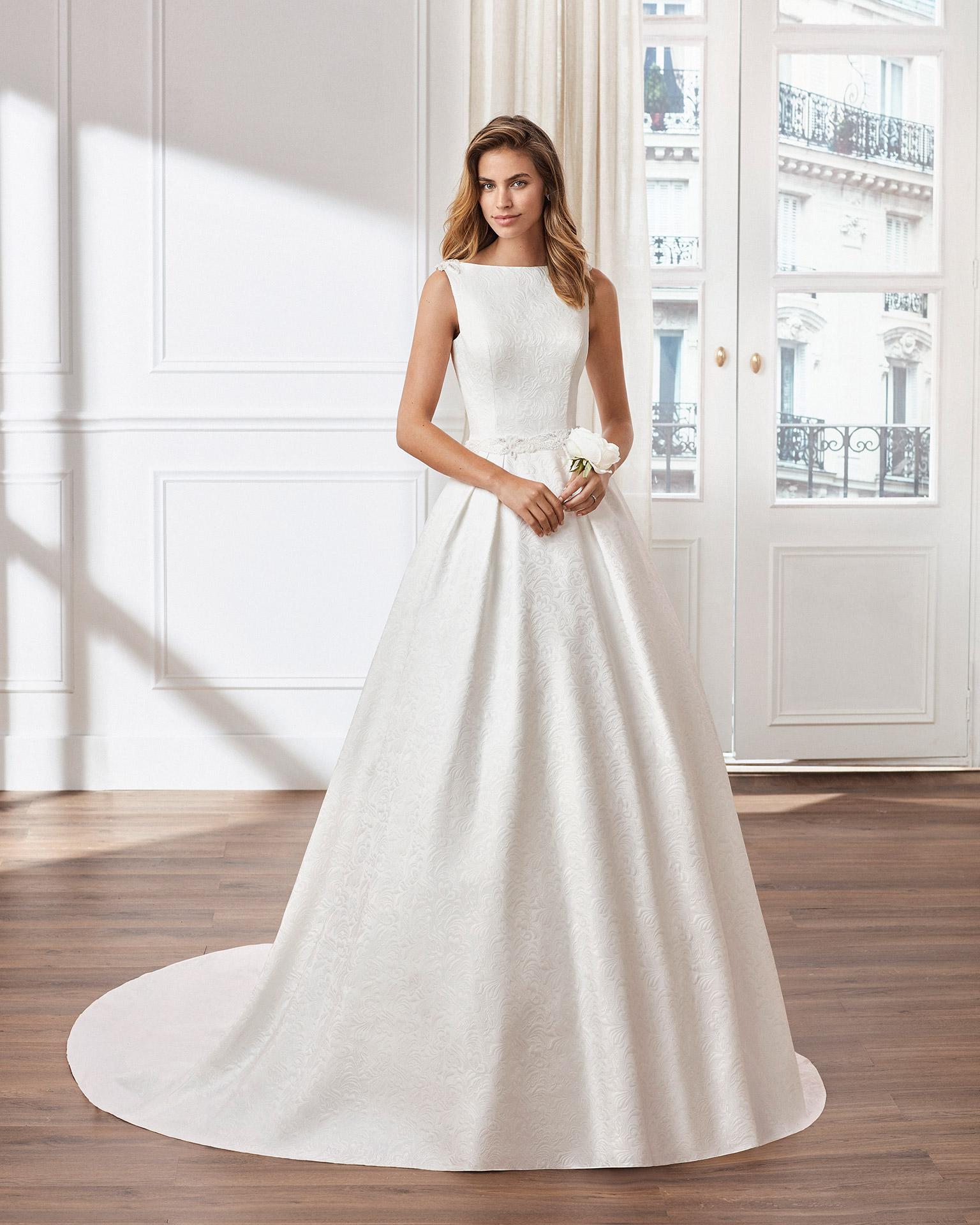 Vestido de novia estilo clásico línea A en brocado. Escote barco y espalda joya. Disponible en color natural. Colección  2020.