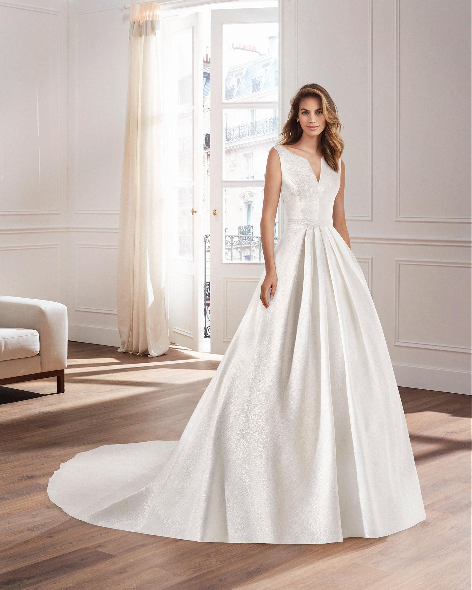 Vestido de novia corte clásico línea A, en brocado con escote pico en delantero y espalda. Colección  2020.