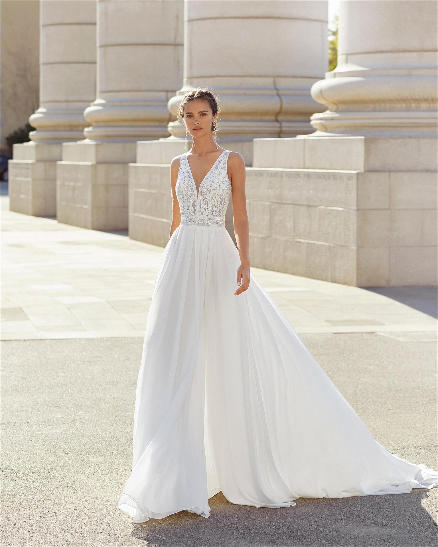 Vestido de novia corte evasé de gasa, encaje y pedrería. Escote en V con espalda transparente de tul plumeti y abertura lateral en falda. Colección  2021.