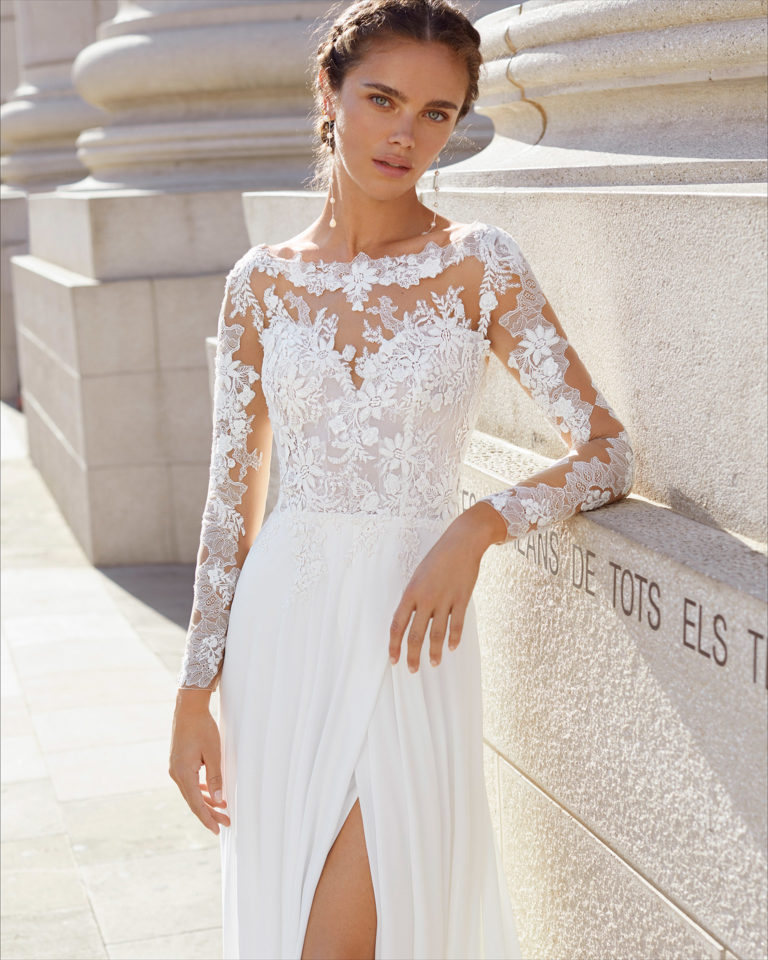 Ballgown-style wedding dress in beaded lace and chiffon. Bateau neckline with sweetheart underlay and V-back. With long sleeves and slit skirt. 2021  Collection.