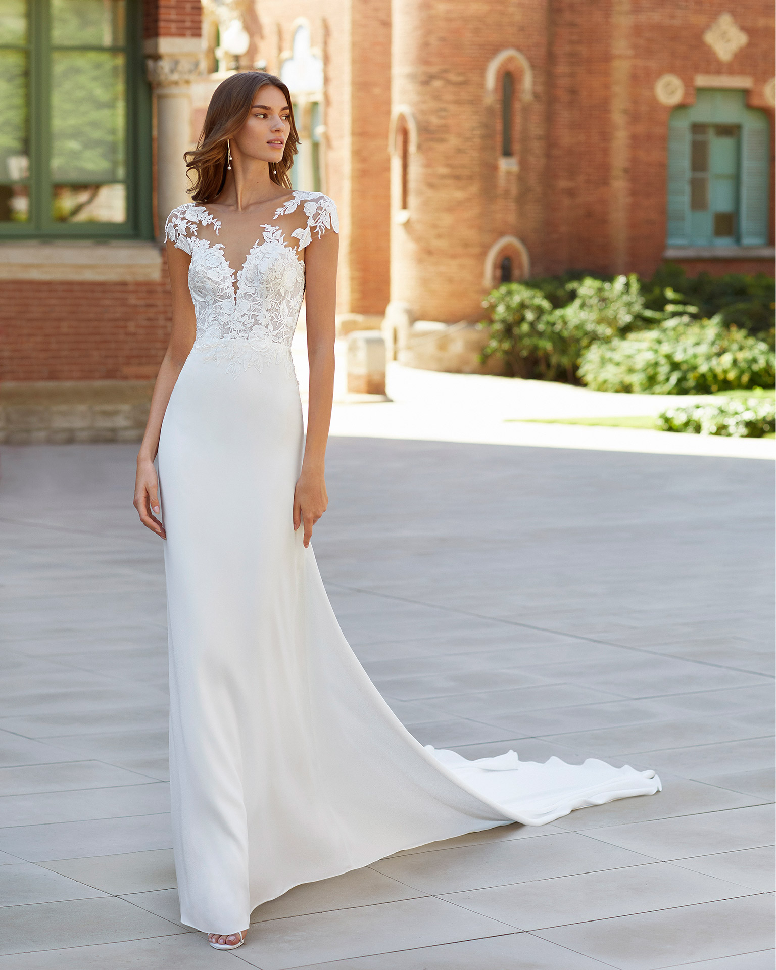 Sheath-style wedding dress in stretch crepe and lace. Deep-plunge neckline with yoke, appliqués on sleeves and open back. 2021  Collection.