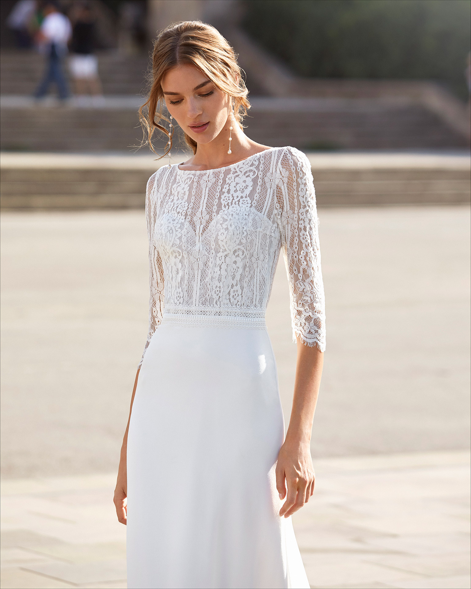 Sheath-style wedding dress in stretch crepe and lace with beading on waist. Bateau neckline with sweetheart underlay, V-back and three-quarter sleeves. 2021  Collection.