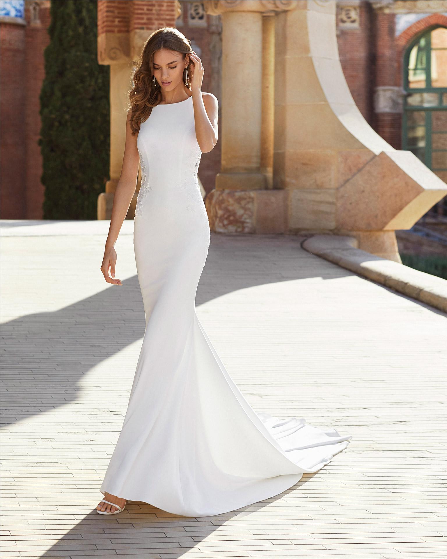 Vestido de novia corte sirena de crep elástico, encaje y pedrería. Escote barco y espalda escotada con transparencias en costados. Colección  2021.