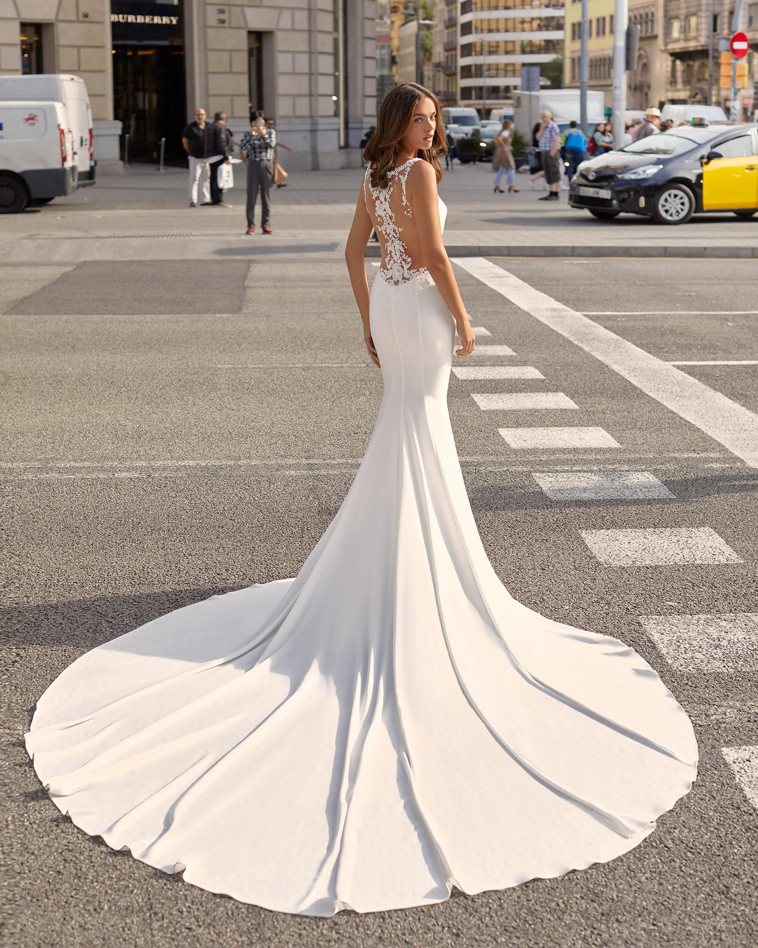 Vestido de novia corte sirena de crep elástico, encaje y pedrería. Escote en V y espalda transparente con aplicaciones. Colección  2021.