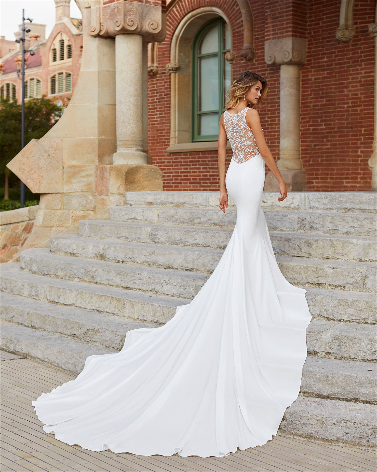 Mermaid-style wedding dress in stretch crepe with beading. Bateau neckline and sheer beaded back. 2021  Collection.