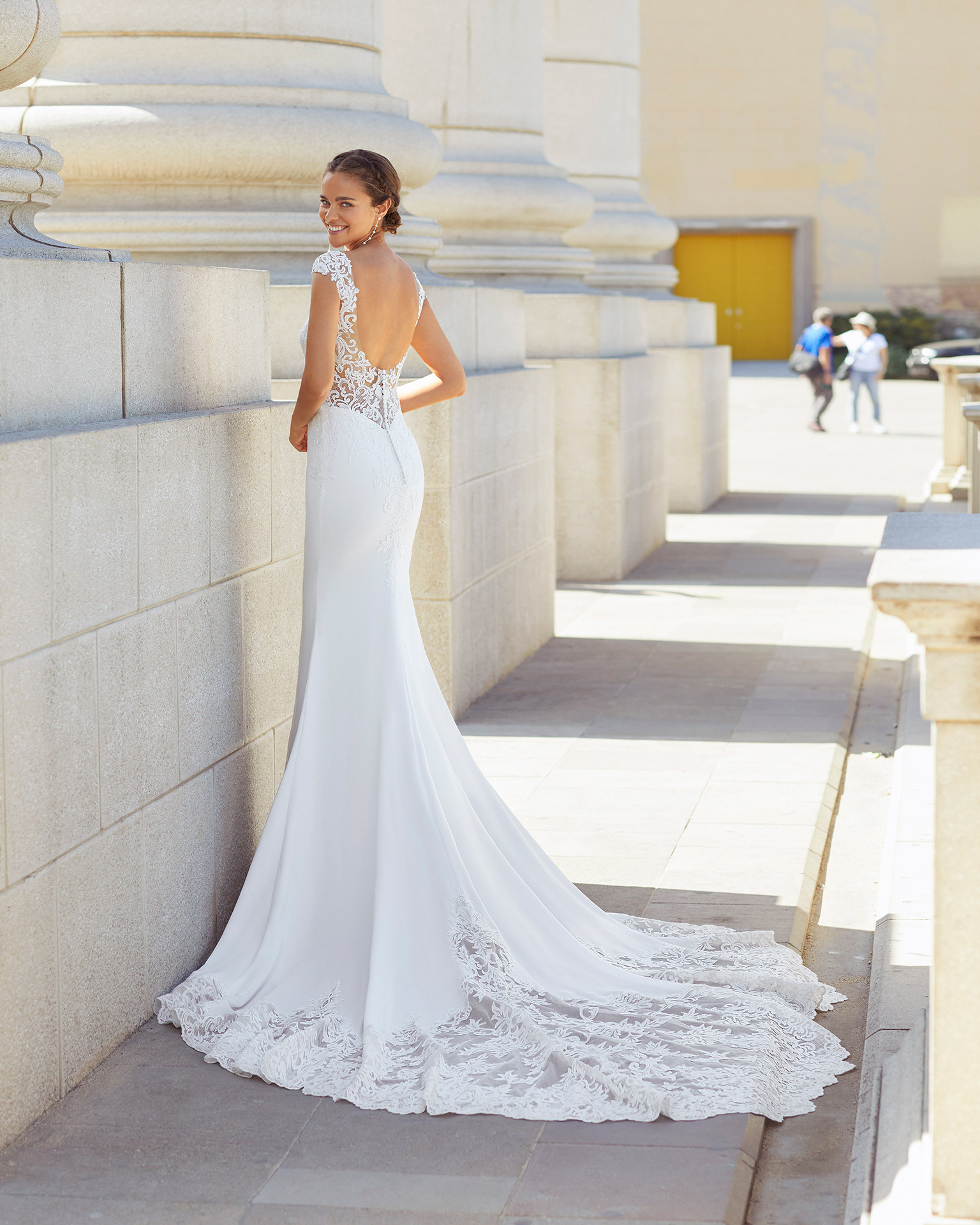 Sheath-style wedding dress in stretch crepe and lace. Bateau neckline with sweetheart underlay, low back, short sleeves with appliqués and trefoil train. 2021  Collection.