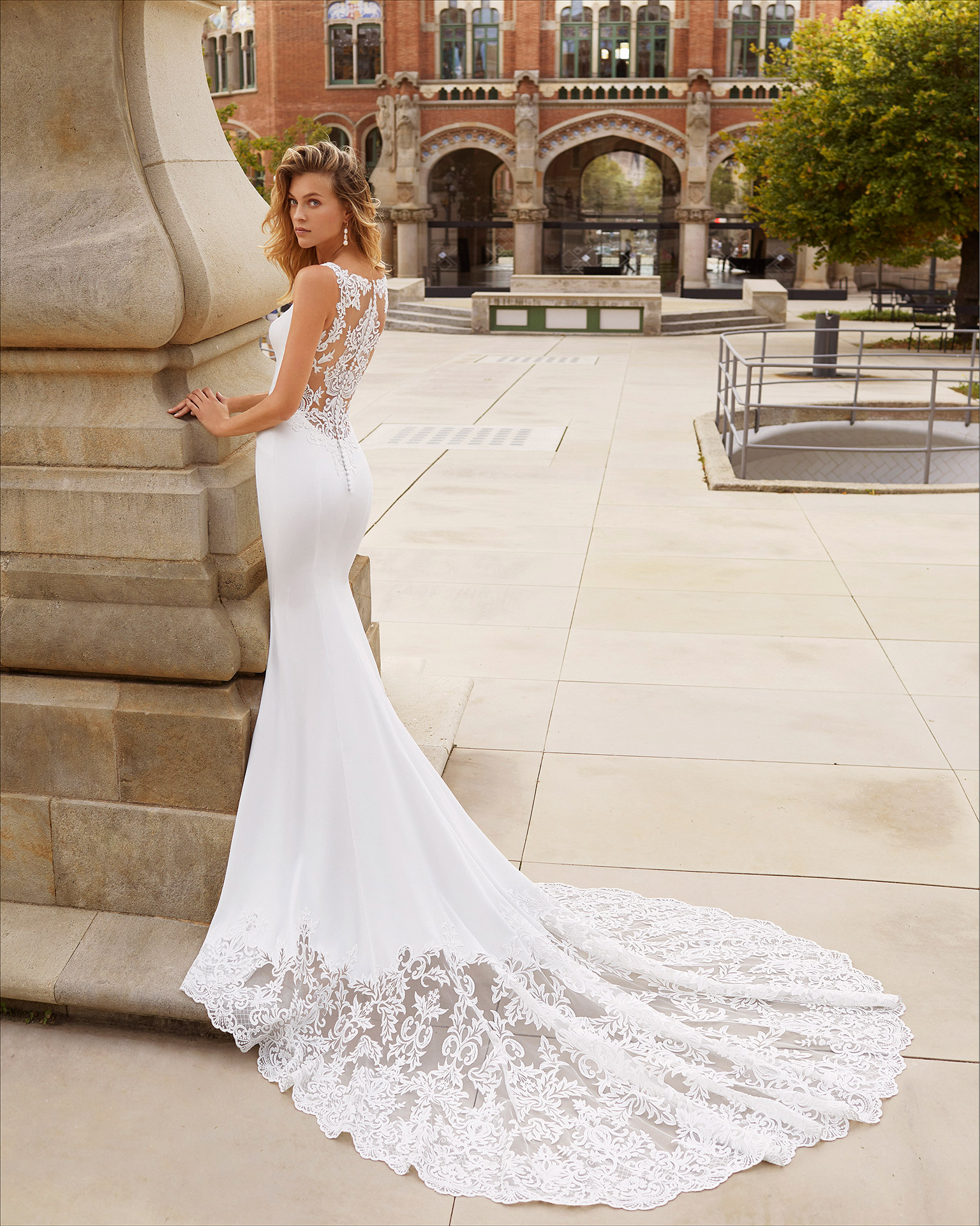 Mermaid-style wedding dress in stretch crepe and lace. V-neckline and sheer back with lace. 2021  Collection.