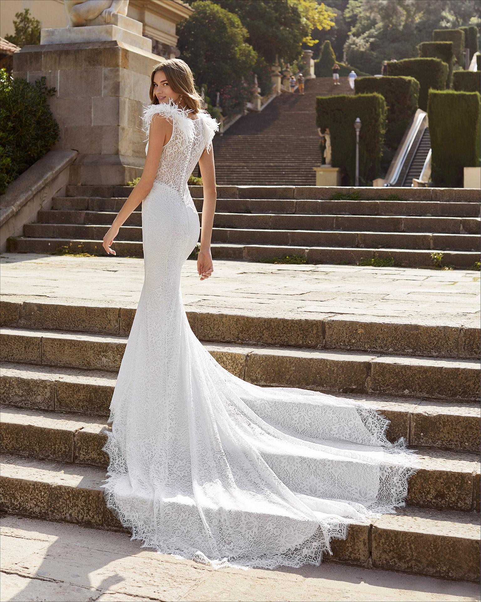 Vestido de novia corte sirena de encaje. Escote en V y espalda cerrada de encaje con plumas en hombros y pedrería en escote, sisas y cintura. Colección  2021.