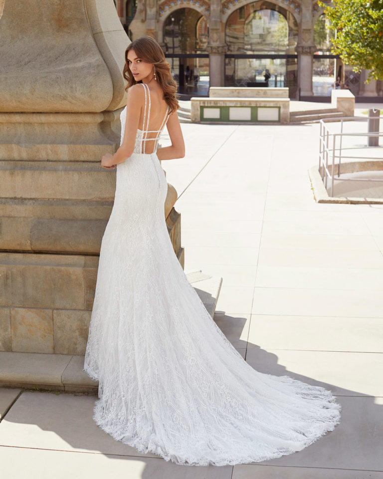 Sheath-style wedding dress in beaded lace. V-neckline and open back with shoulder straps. 2021  Collection.