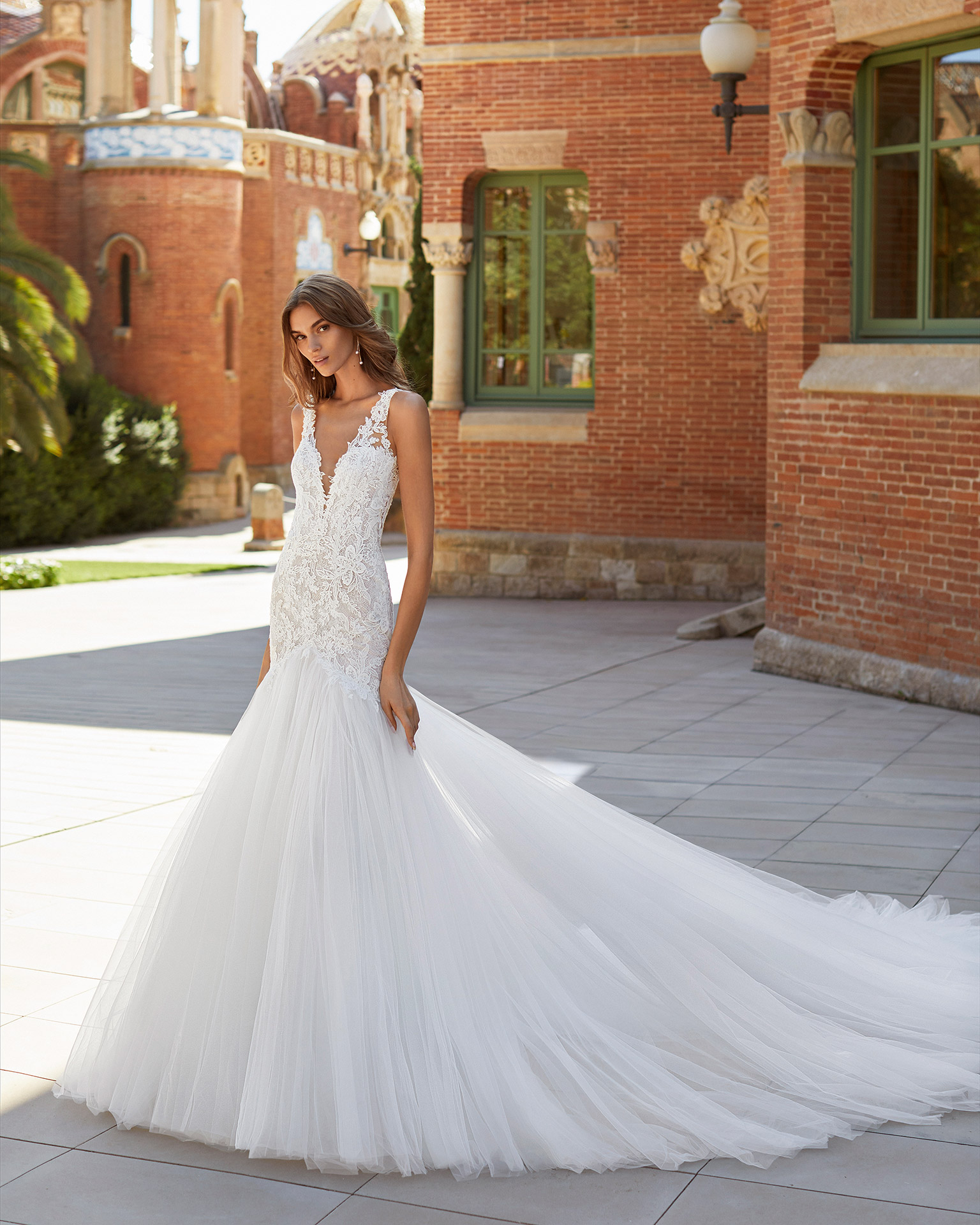 Mermaid-style wedding dress in tulle and lace. Deep-plunge neckline and open back. 2021  Collection.