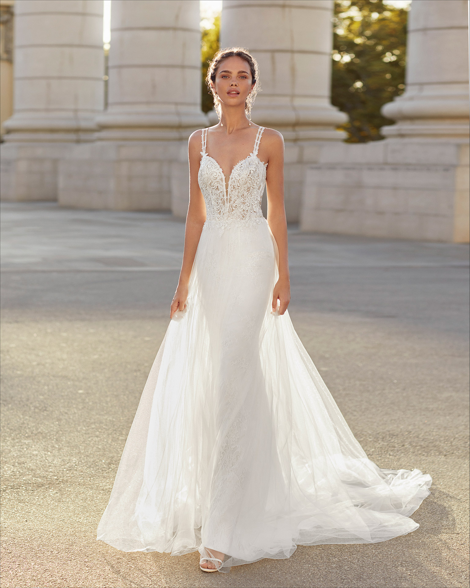 Sheath-style wedding dress in tulle and beaded lace. Deep-plunge neckline and open back with crossover shoulder straps. 2021  Collection.