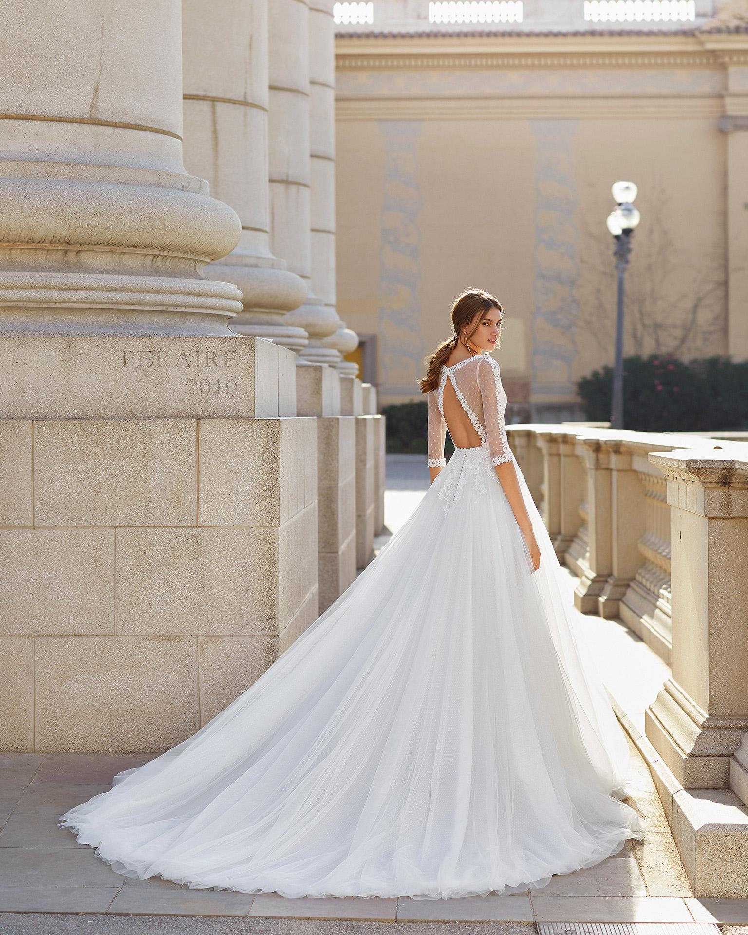 Vestido de novia estilo romántico de tul plumeti, encaje y pedrería. Escote en V y espalda de tul plumeti con abertura y manga 3/4. Colección  2021.