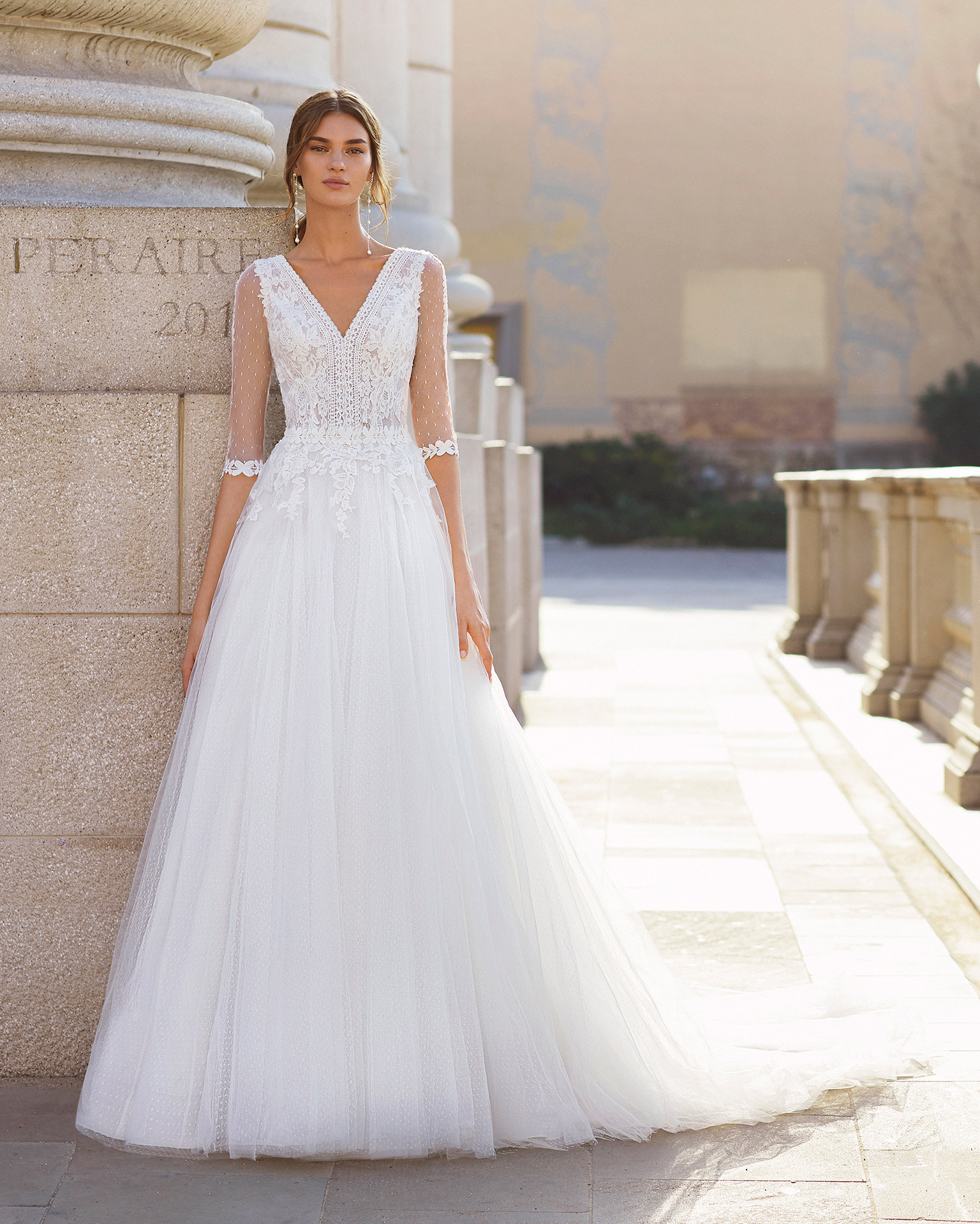 Romantic-style wedding dress in dot tulle and beaded lace. V-neckline, back in dot tulle with opening and three-quarter sleeves. 2021  Collection.