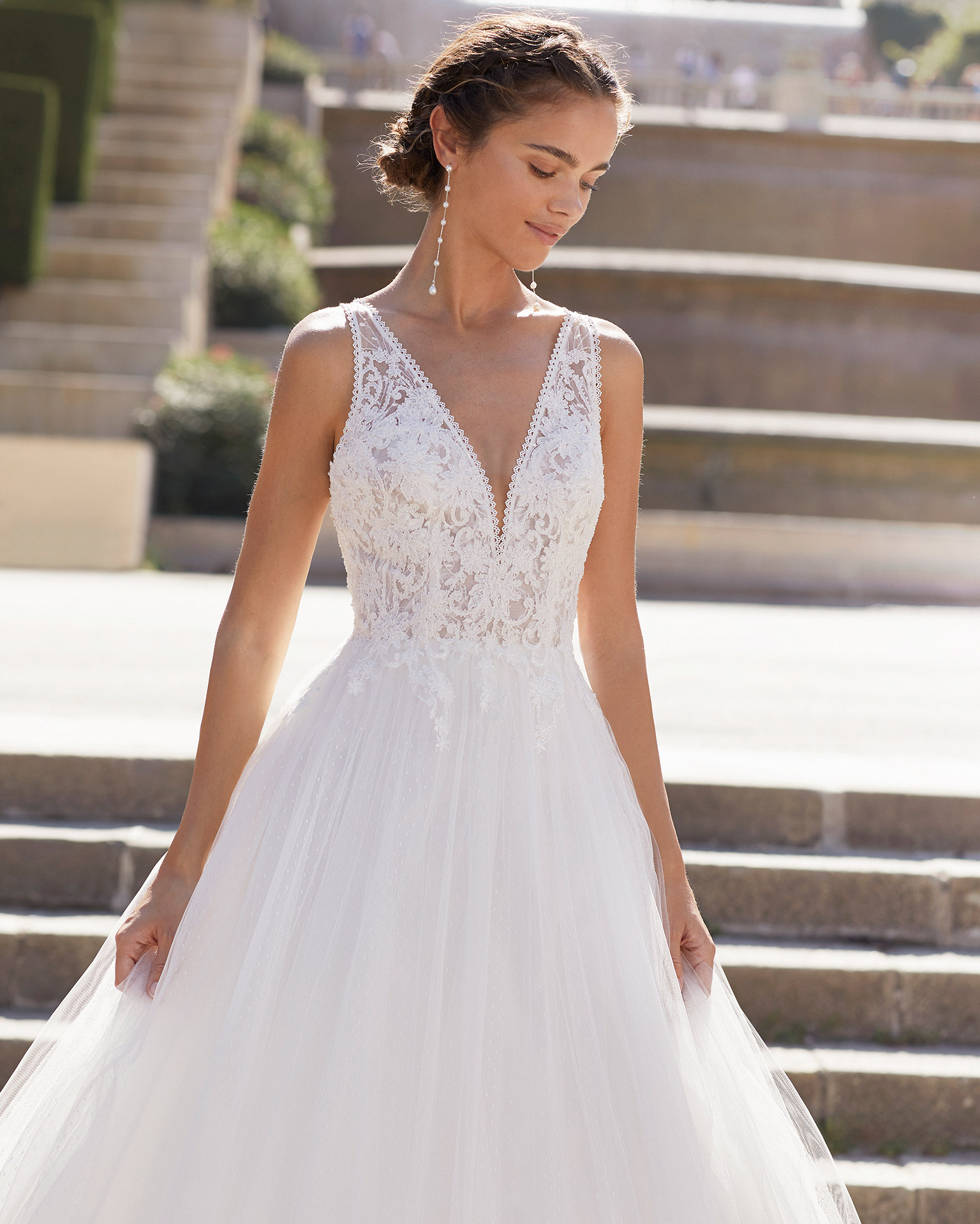 Romantic-style wedding dress in dot tulle and beaded lace. V-neckline and low back with crossover shoulder straps. 2021  Collection.