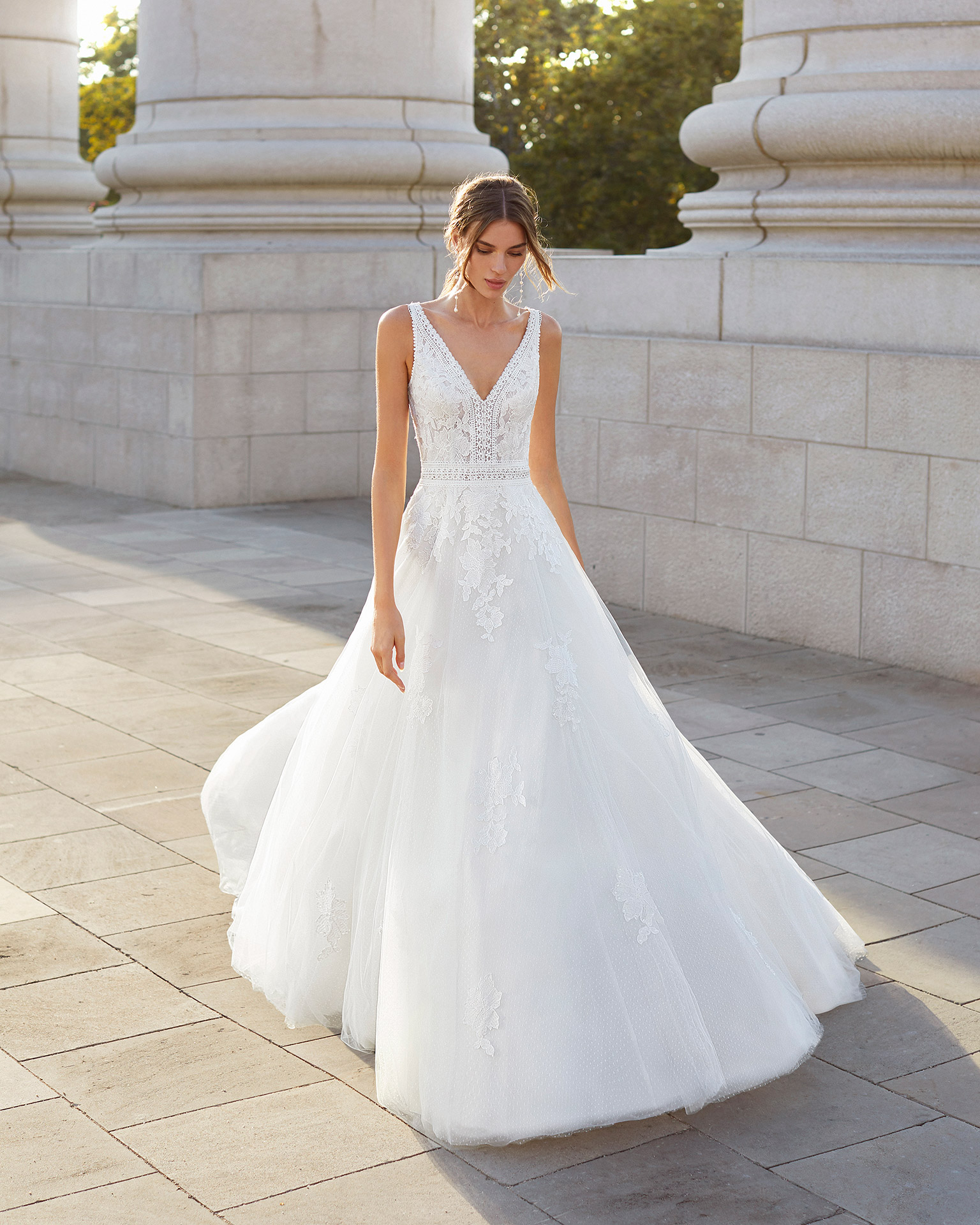 Ballgown-style wedding dress in dot tulle and beaded lace. V-neckline and slit back. 2021  Collection.