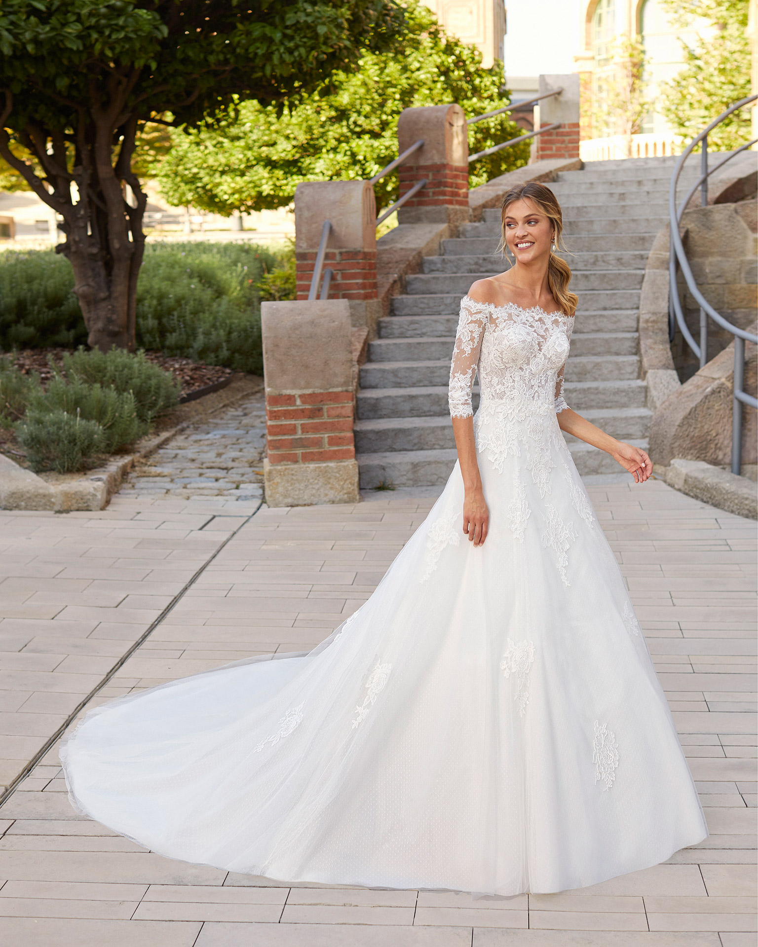 Princess-style wedding dress in dot tulle and beaded lace. Off-the-shoulder neckline with sweetheart underlay and three-quarter sleeves. 2021  Collection.