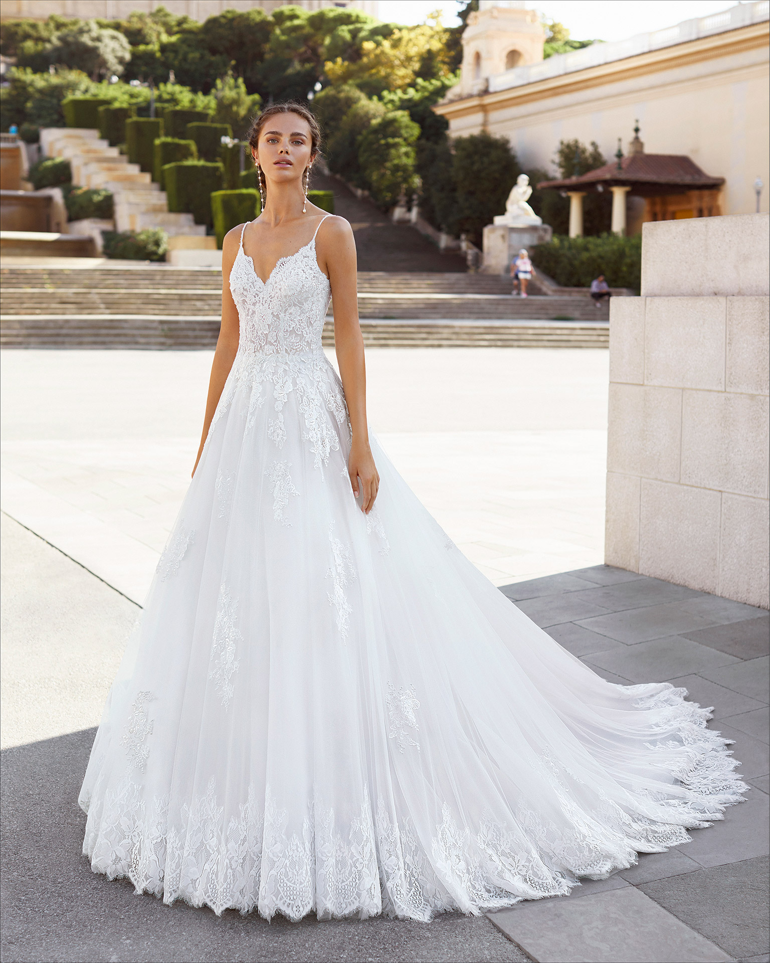 Romantic-style wedding dress in tulle and beaded lace. V-neckline and low back with spaghetti shoulder straps. 2021  Collection.