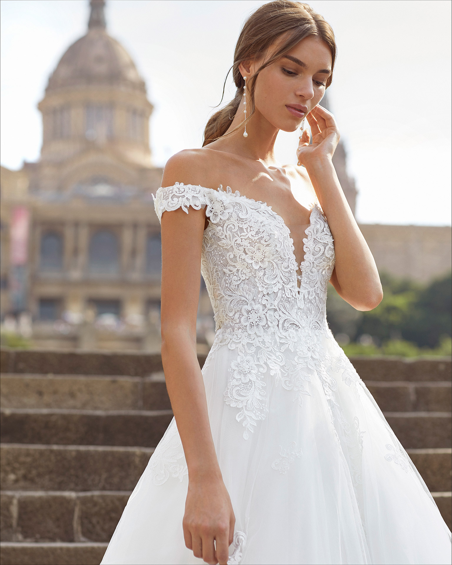 Princess-style wedding dress in beaded lace and tulle. Deep-plunge neckline with off-the-shoulder straps. 2021  Collection.