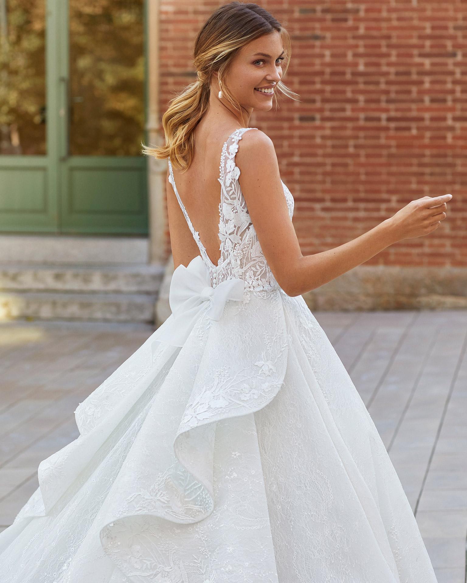 Vestido de novia estilo princesa de encaje y pedrería. Escote en pico y espalda escotada con un lazo. Colección  2021.