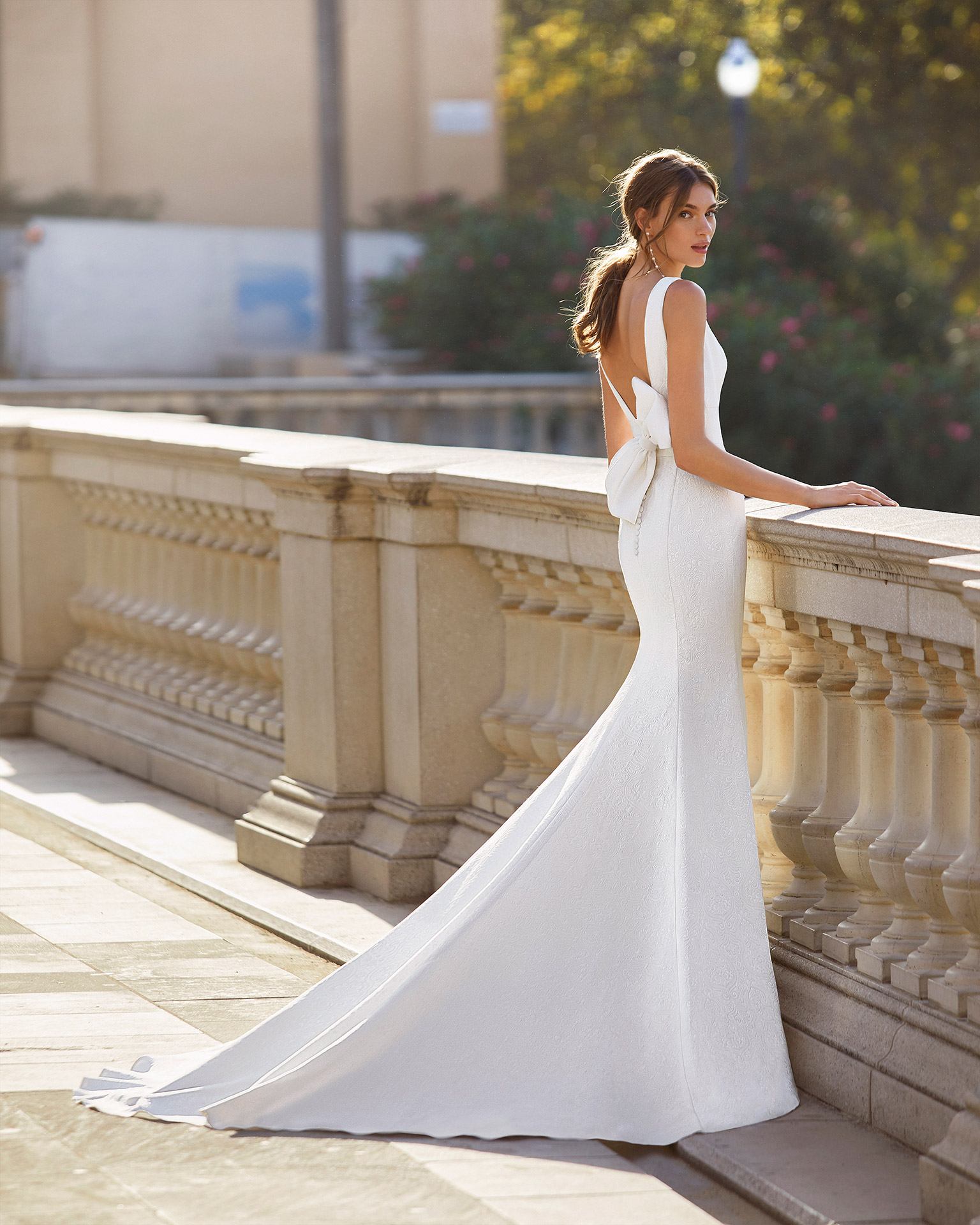 Classic-style wedding dress in brocade with deep-plunge neckline and U-back with bow. 2021  Collection.