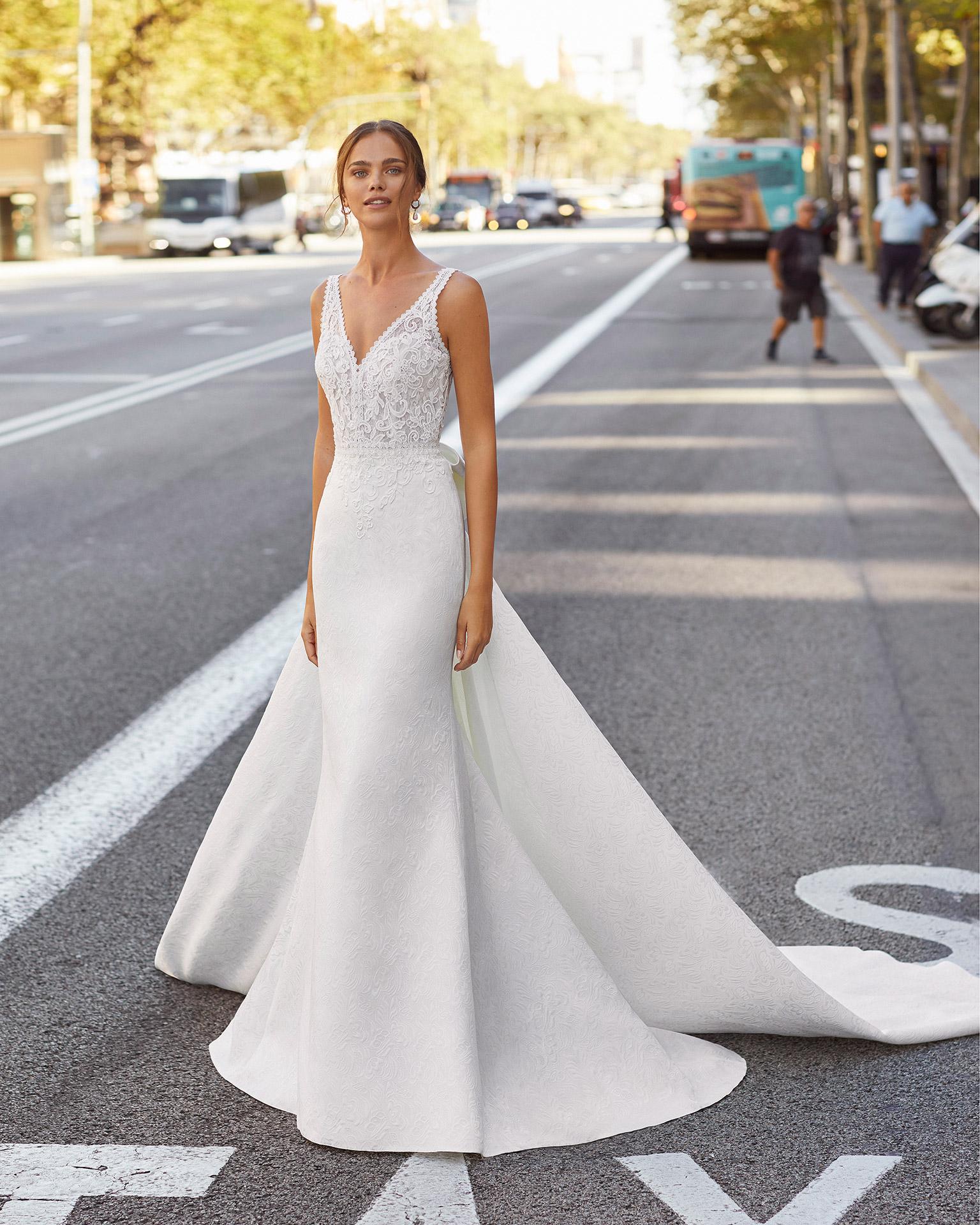 Vestido y cola de novia estilo clásico de brocado, encaje y pedrería en cintura. Con escote y espalda en V y lazo en la cola. Colección  2021.