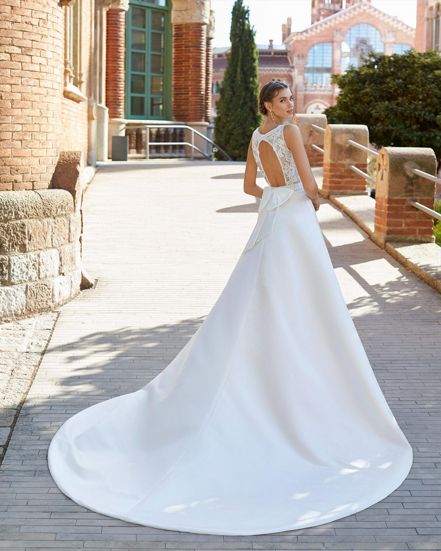 Vestido de novia estilo clásico de raso, encaje y pedrería en cintura y escote. Escote redondo y espalda escotada con lazo. Colección  2021.