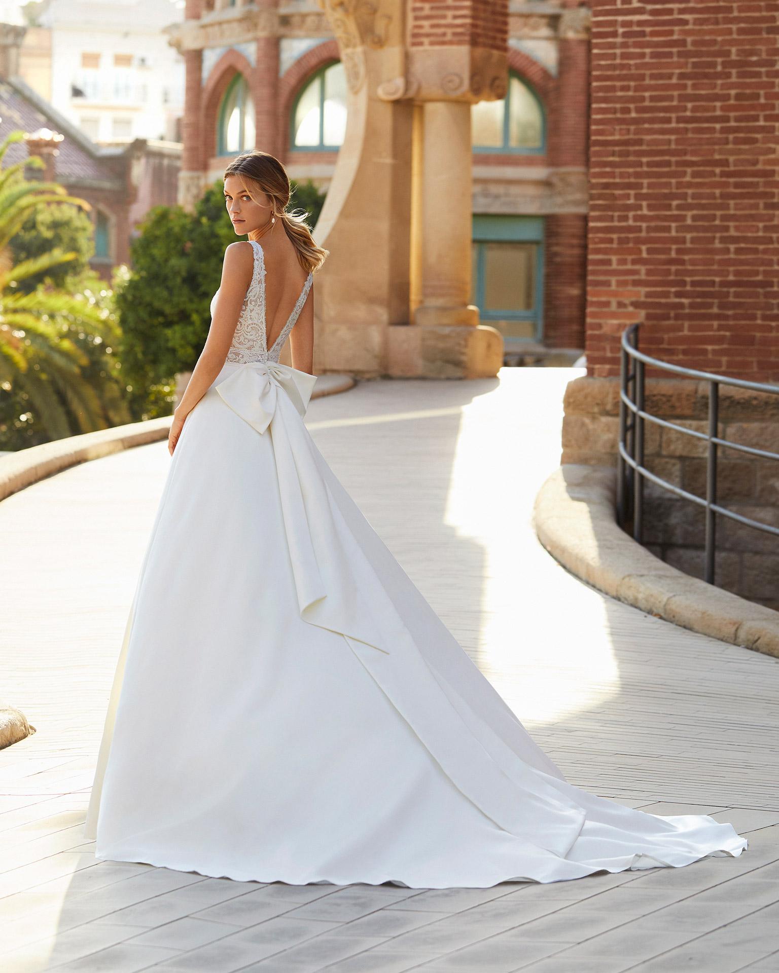 Vestido de novia estilo clásico de raso, encaje y pedrería. Escote y espalda en V con lazo en espalda. Colección  2021.