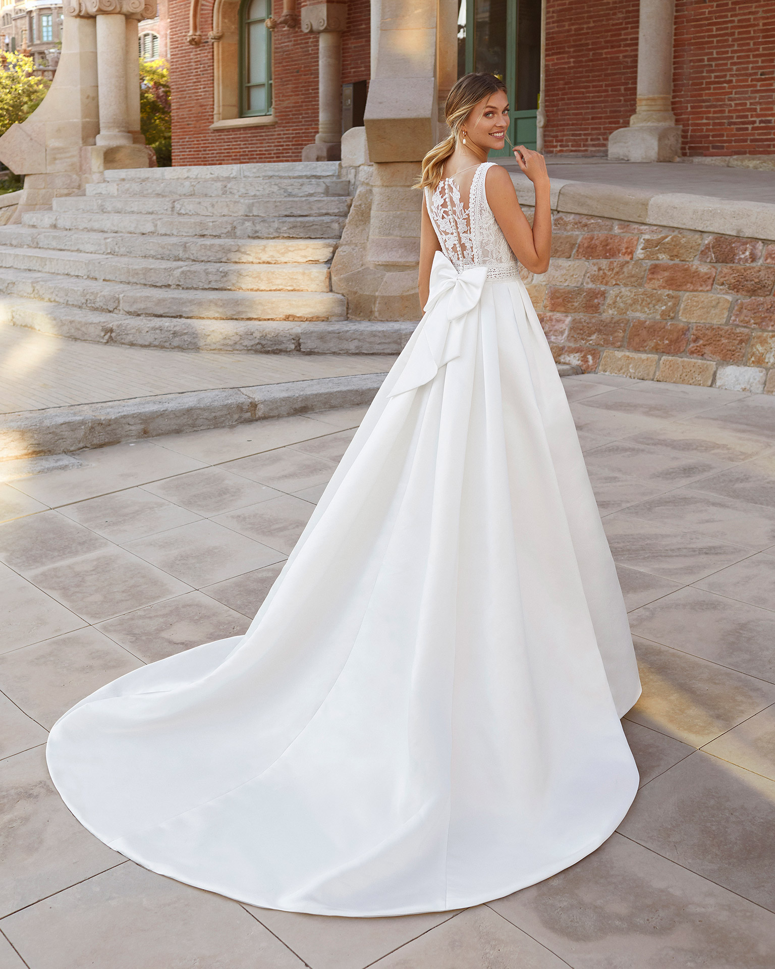 Classic-style wedding dress in satin with beaded lace on neckline and waist. V-neckline and sheer back in lace, with pockets and bow. 2021  Collection.