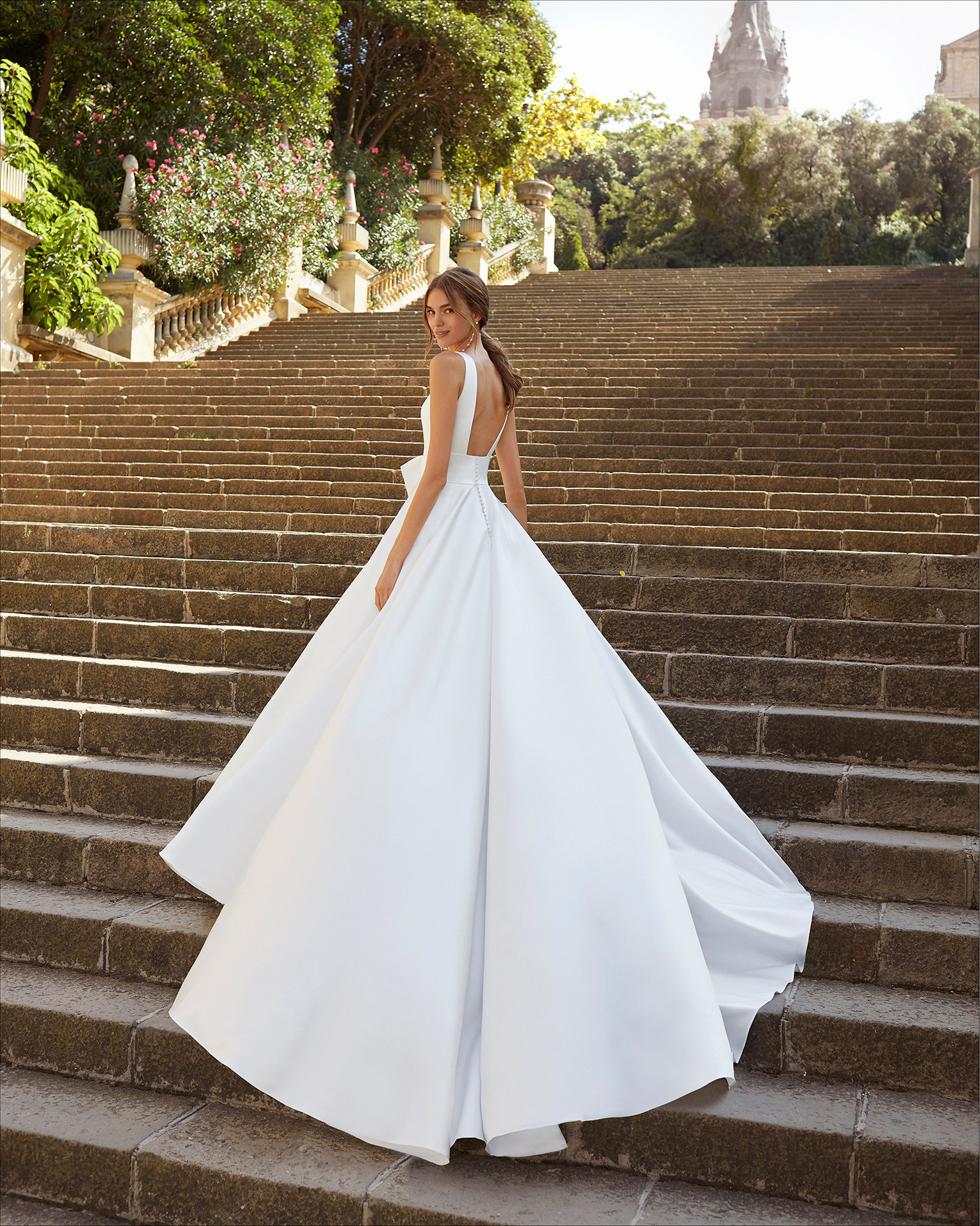 Classic-style wedding dress in satin. Deep-plunge neckline and U-back, with front bow at waist and pockets. 2021  Collection.